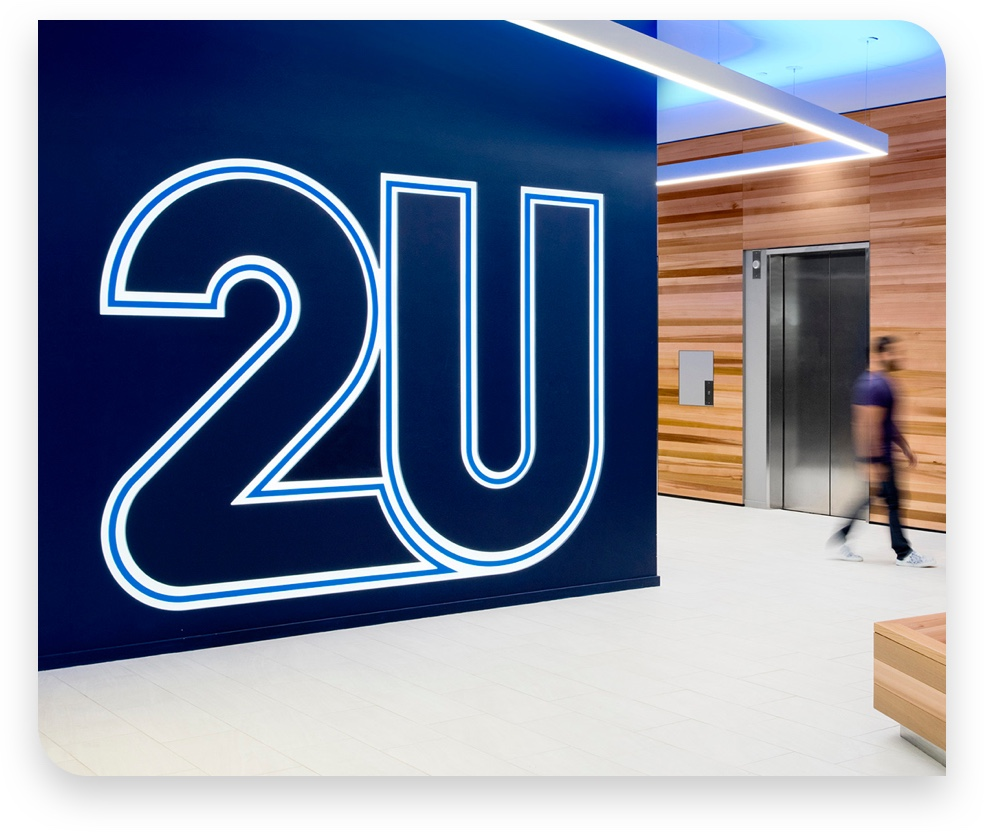 2U logo on a wall in a hallway with man walking in background
